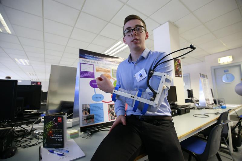A student shows off their bionic arm project